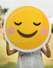 person holding round smiling emoji board photo